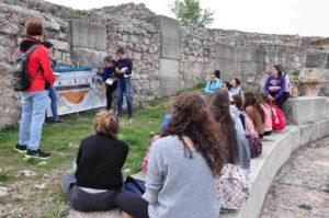 Alumnos del Colegio Claret de Segovia explicando a sus compañeros la estructura del teatro de Segóbriga.